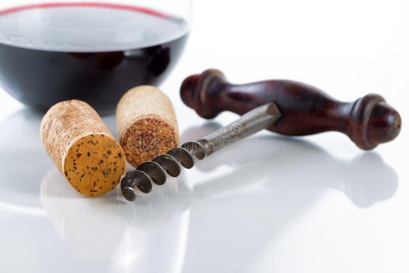 Vieux tire-bouchon avec des lièges et vin rouge en verre sur la table photos libres de droits