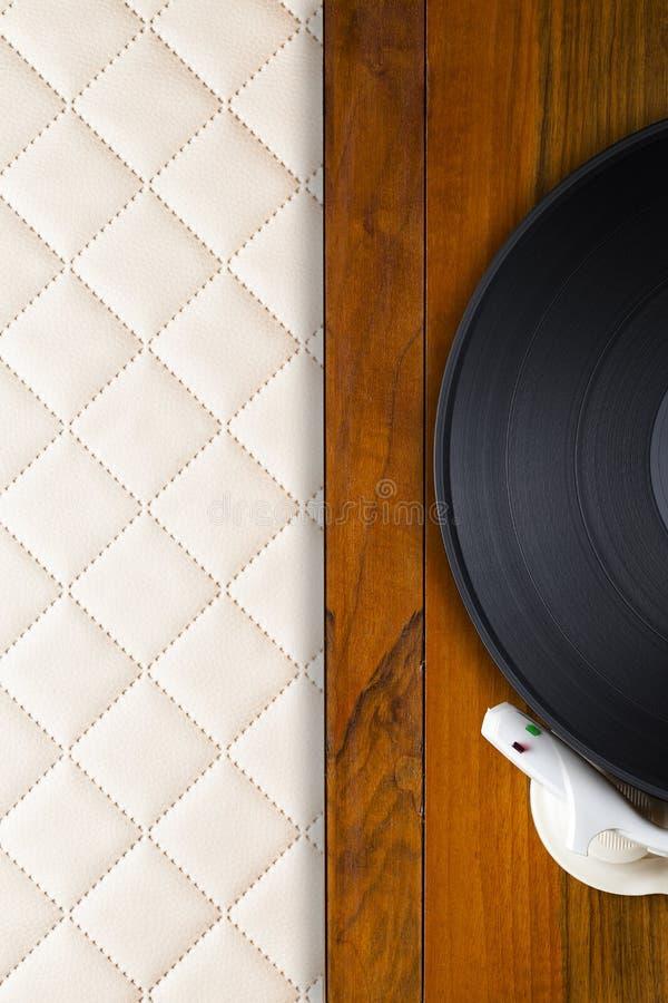 Vieux tourne-disque et disque vinyle en bois classiques sur le fond en cuir photo libre de droits