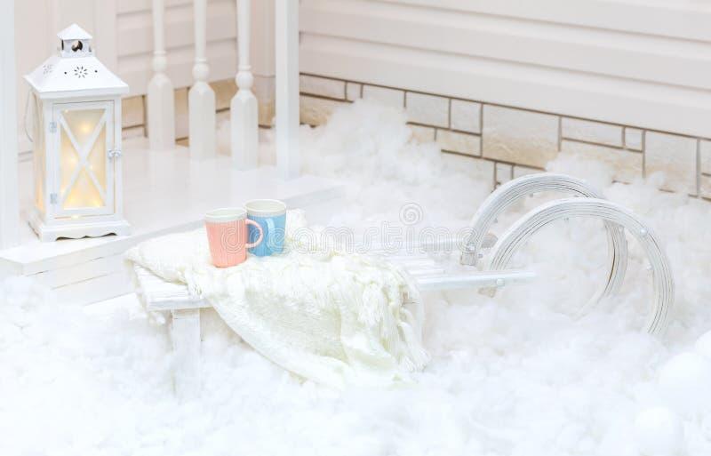 Vieux traîneau blanc de vintage avec la fourrure se tenant près de la maison dans la neige en hiver Décorations de Noël images stock