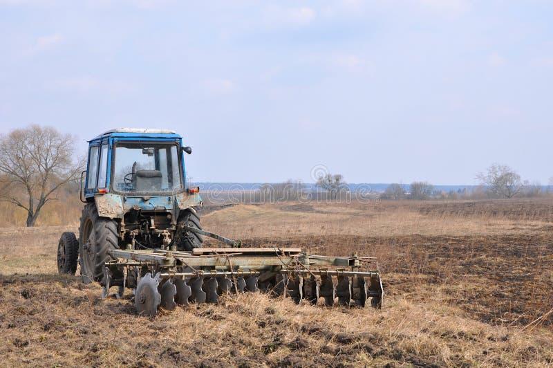 Vieux tracteur avec la herse rouillée images stock
