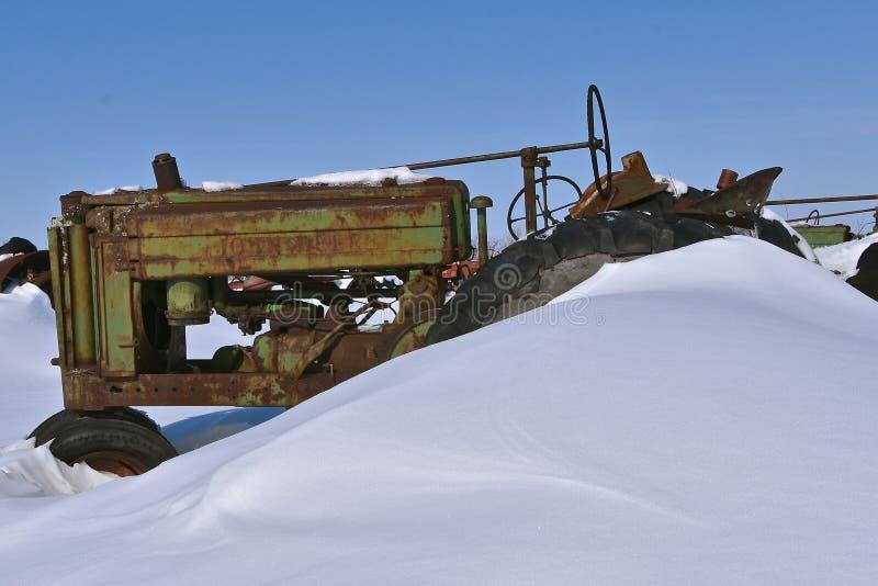 Vieux tracteur de John Deere enterré dans la neige image stock