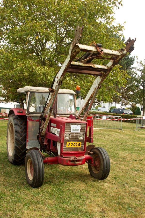 Vieux tracteur rouge avec l'équipement de levage image stock