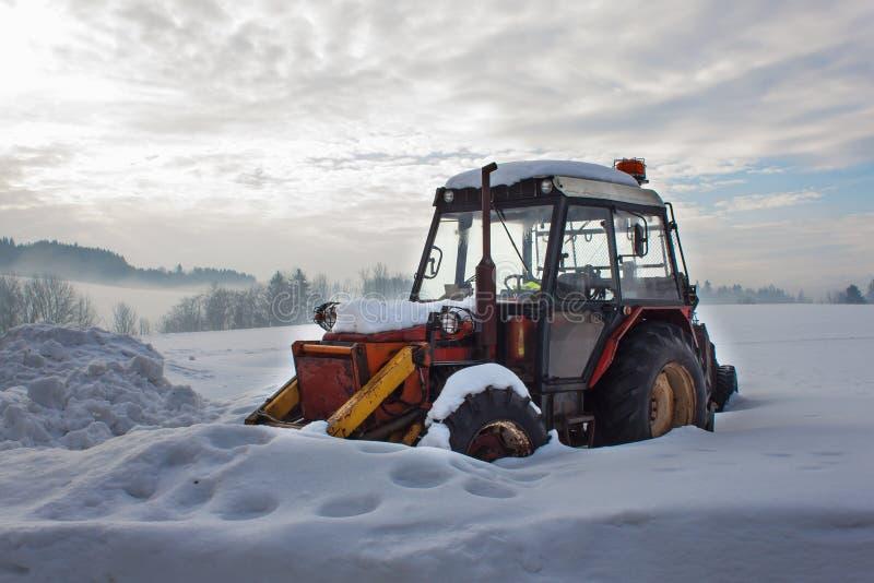Vieux tracteur sous la neige Calamité de neige dans le transport Moteur diesel congelé photographie stock
