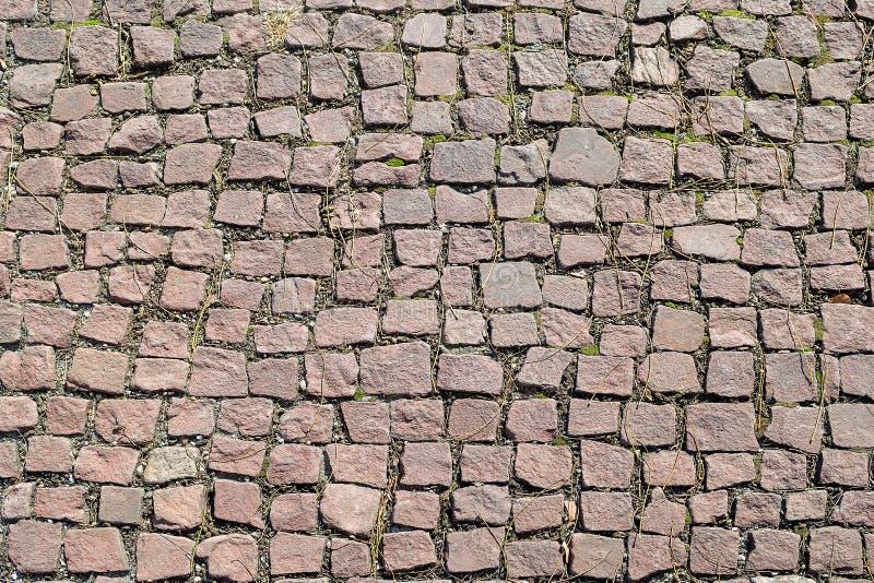 Vieux trottoir de pavé rond, pavé avec la texture de pierres, historique et architecturale rougeâtre pour le fond photo stock