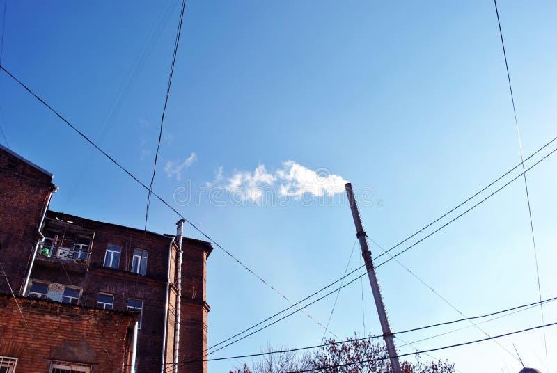 Vieux tuyau avec de la fumée, coin rouge d'immeuble de brique avec des fenêtres et fils sur le fond lumineux de ciel bleu d'hiver image libre de droits