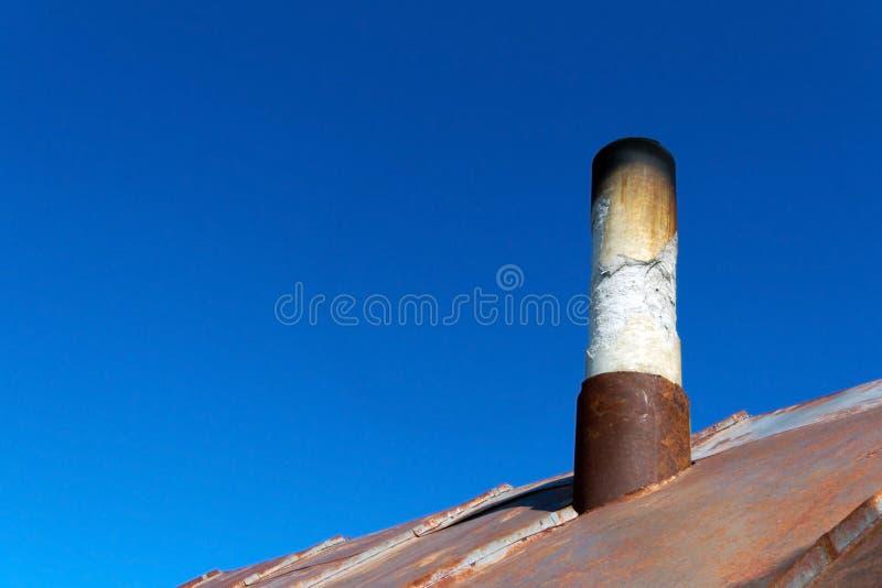 Vieux tuyau de fumée hors du toit rouillé de fer image libre de droits