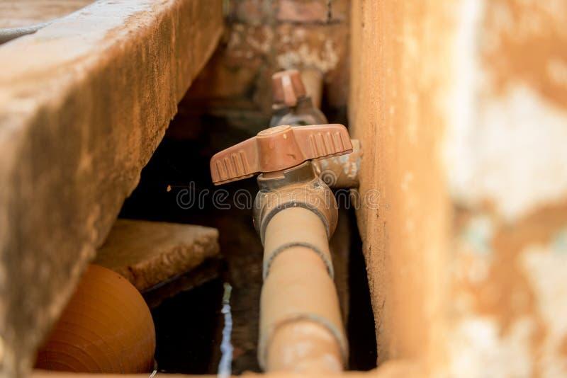 Vieux tuyau de PVC de cru en gros plan avec la valve rouge sur le mur en béton sale - approvisionnement en eau photographie stock