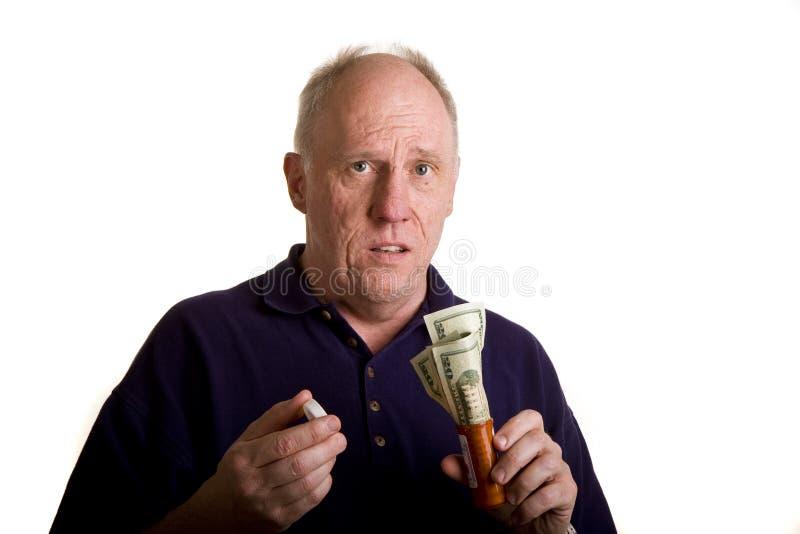 Vieux type avec de l'argent dans la bouteille de prescription photographie stock libre de droits