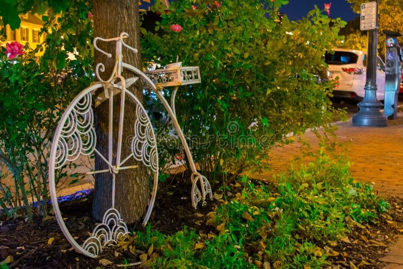Vieux vélo sur rail blanc se penchant sur un arbre la nuit sur la tache floue Backgrou images stock