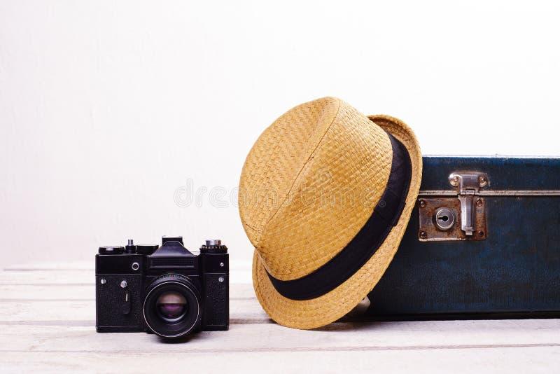 Vieux valise et appareil-photo de chapeau de paille sur le plancher en bois blanc près du mur photographie stock