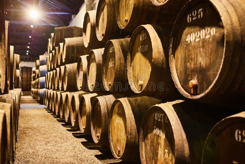 Vieux a vieilli les barils en bois traditionnels avec du vin dans une chambre forte align?e dans la cave fra?che et fonc?e en Ita image stock