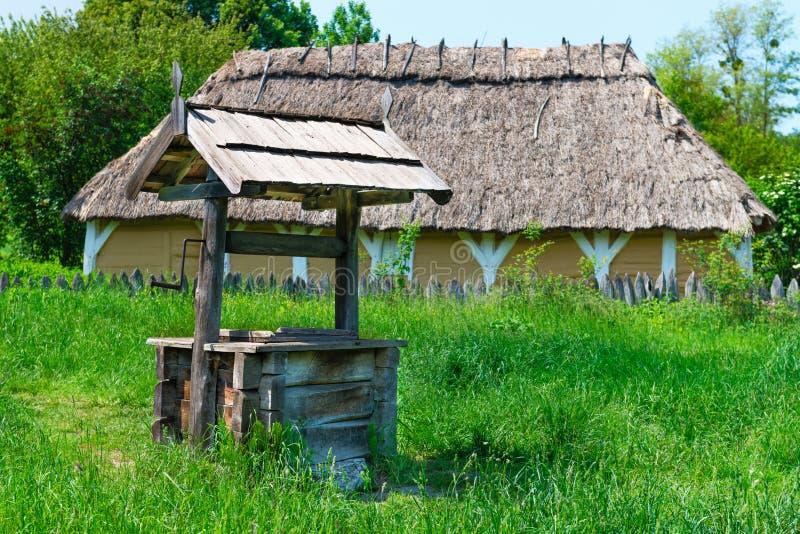 Vieux village bien avec un toit en bois images stock