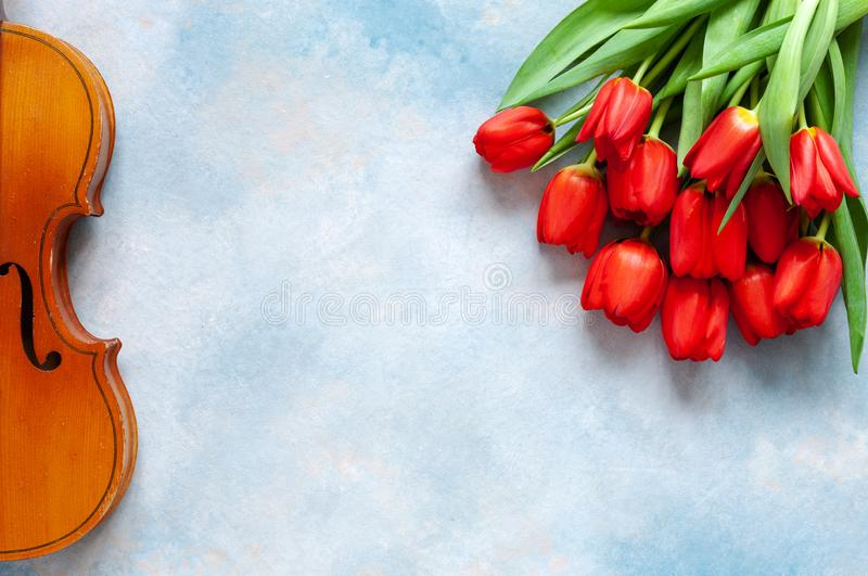 Vieux violon et bouquet des tulipes rouges Saint Valentin, le 8 mars concept Vue supérieure, en gros plan sur le fond concret de  photos libres de droits
