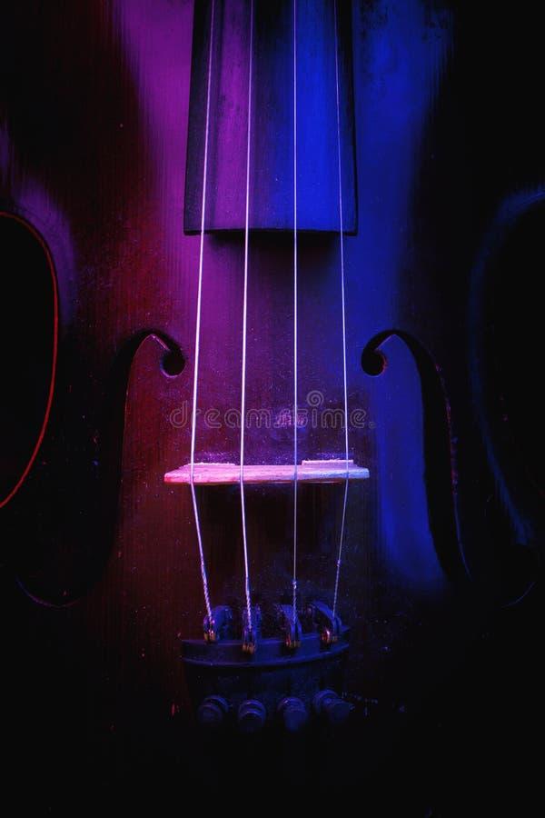 Vieux violon illuminé dans bleu et pourpre photos libres de droits