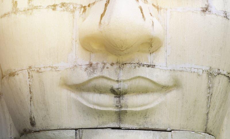 Vieux visage blanc de sculpture en plan rapproché avec la lumière chaude de cru images stock