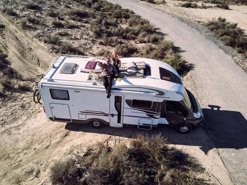 Married couple sitting on the roof of camper royalty free stock photography