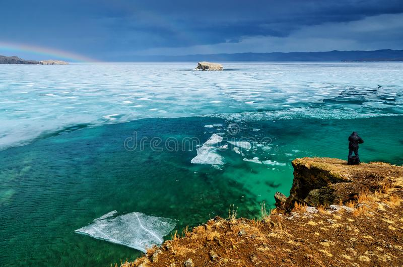 View above big beautiful lake Baikal with Ice floes floating on the water and mens back is taking photos, Russia. Maloye sea stock image