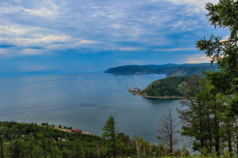 View above big beautiful lake, Baikal lake, Russia. Summer Sunny day. The sky is covered with thick clouds. Eastern Siberia stock photos