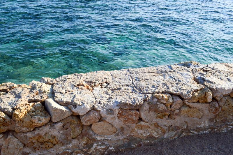 View from above of the blue sea, water with a coral bottom from a stone old ancient crumbling wall of cobblestones. royalty free stock images