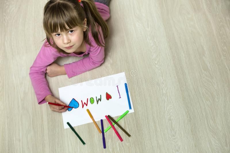 View from above of cute child girl drawing with colorful crayons I love Mom on white paper. Art education, creativity concept royalty free stock images