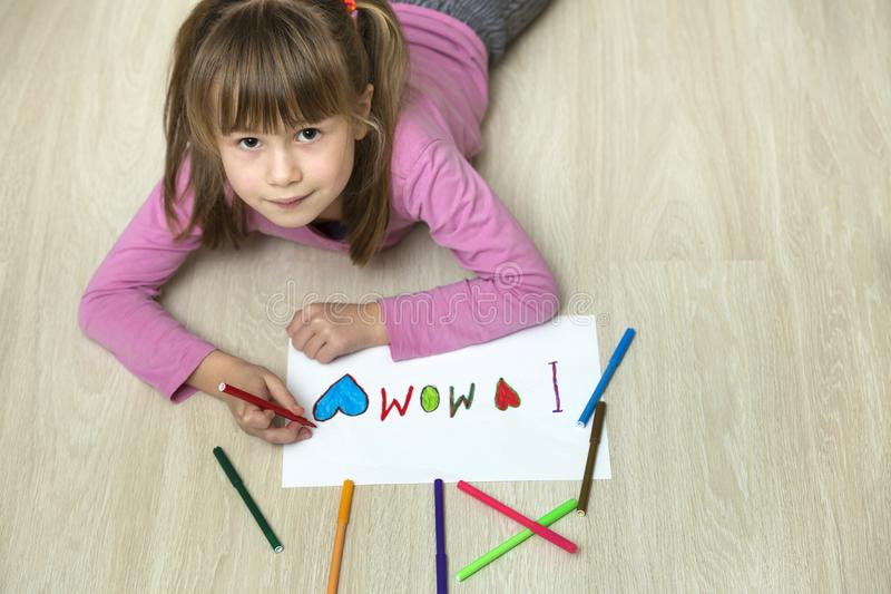 View from above of cute child girl drawing with colorful crayons I love Mom on white paper. Art education, creativity concept stock photo