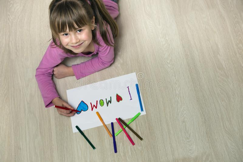 View from above of cute child girl drawing with colorful crayons I love Mom on white paper. Art education, creativity concept royalty free stock photography