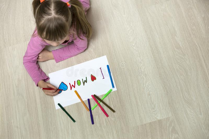 View from above of cute child girl drawing with colorful crayons I love Mom on white paper. Art education, creativity concept stock images