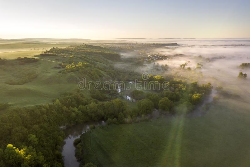 View from above of foggy green hills, village house roofs in valley among green trees under bright blue sky. Spring misty. Landscape panorama at dawn stock photo
