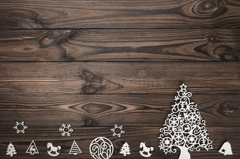 View from above of handmade tree toys on wooden background, greeting card with space for text writing stock image