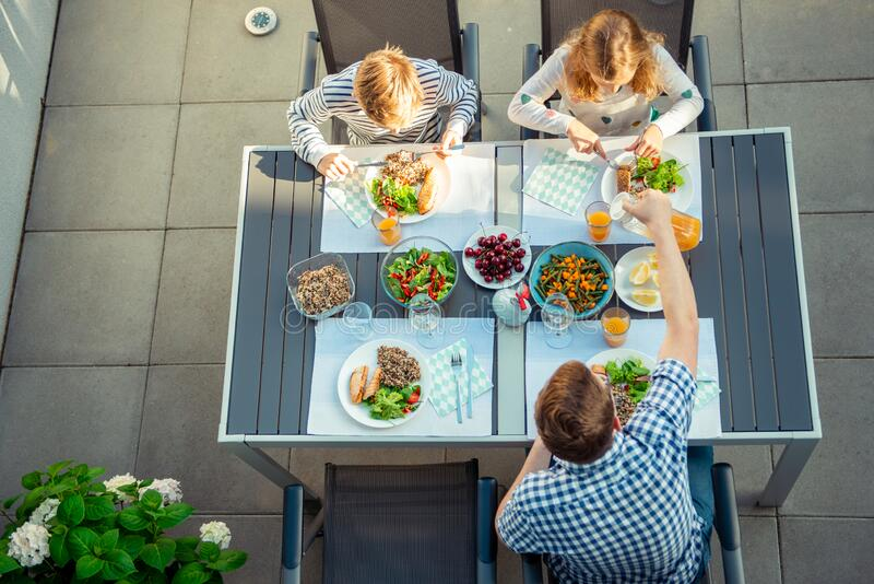 View from above of happy family eating healthy dinner on terrace royalty free stock images