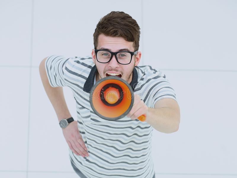 View from above of a happy young man screaming into a megaphone royalty free stock photo