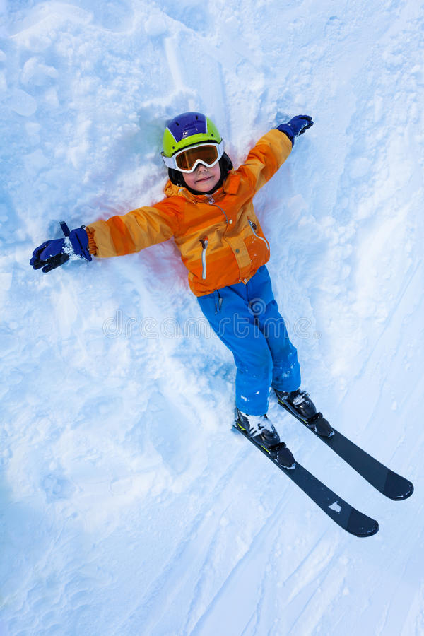 View from above of little boy in ski mask. Little boy lay in snow and looking up with ski mask, mountain ski and helmet view from above stock image