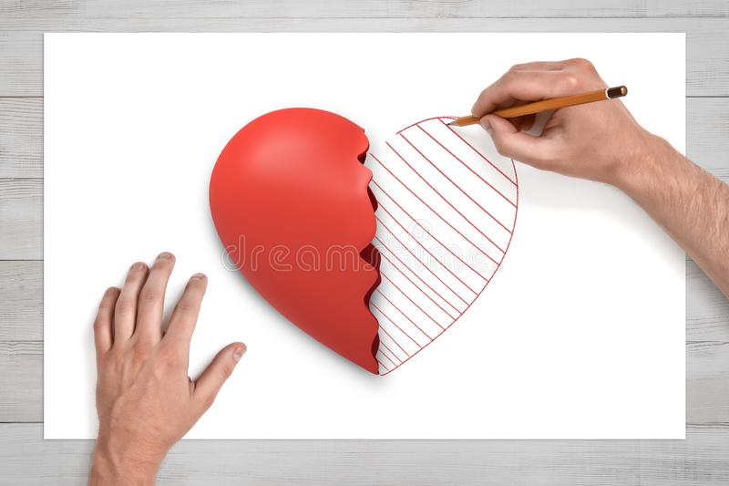 View from above of man`s hands on a desk drawing with a pencil the second half of the broken red heart lying on a white royalty free stock photo