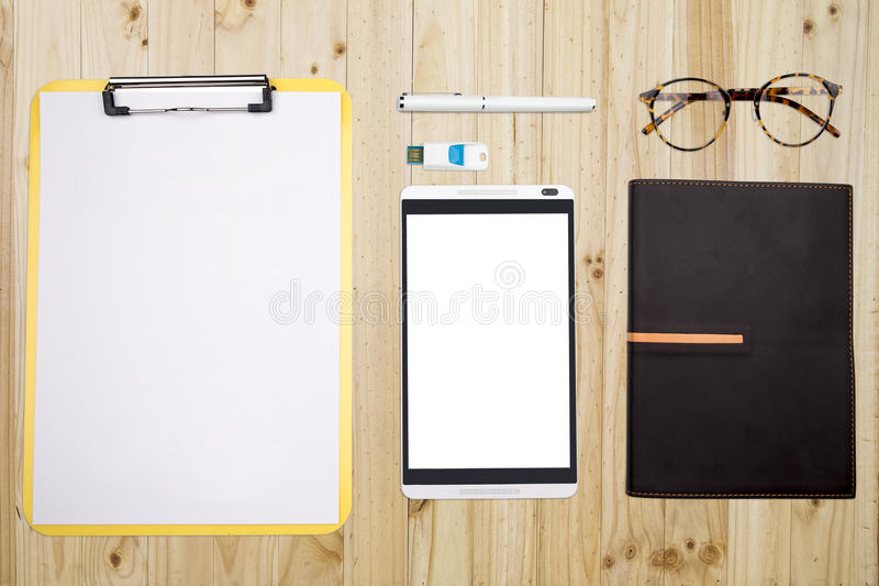 View from above of office supplies and technology divice on a wooden working table background. stock images