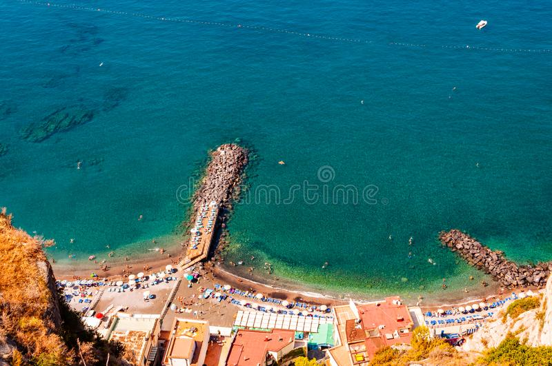 View from above on rocky stones marinas on the beach full of tourists, deckchairs, umbrellas on Tyrrhenian sea bay near Meta and royalty free stock photography