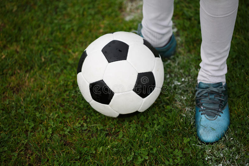 A classic football ball and feet of a young boy on a field background. Children training soccer. A ball on a grass. royalty free stock image