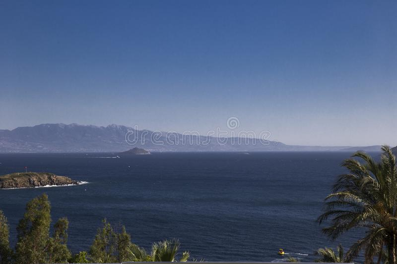 A view from above on small islands in the sea and mountains in t. He background in the morning haze stock photos