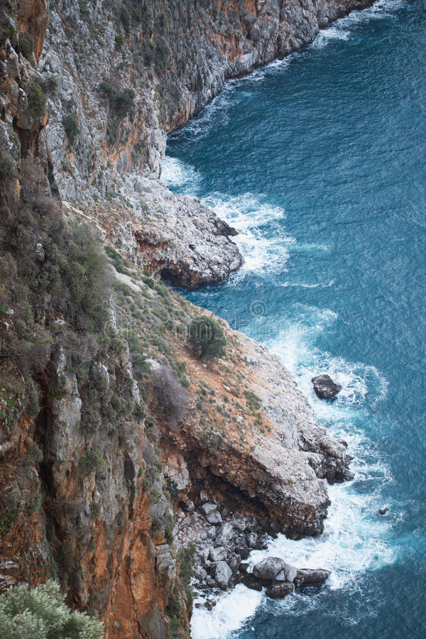 View from above of steep slopes with pine trees and rocky Mediterranean sea shore. Shore, sea, coast, travel, rock, rocky, steep, beach, cliff, water, coastline royalty free stock photo