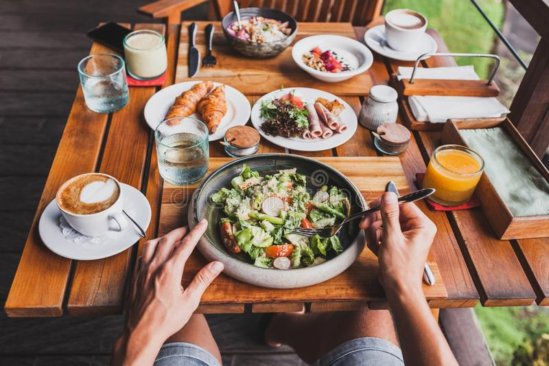 View from above on table with breakfast, man hands. View from above on table with fresh breakfast. Man hands holding fork and knife royalty free stock images