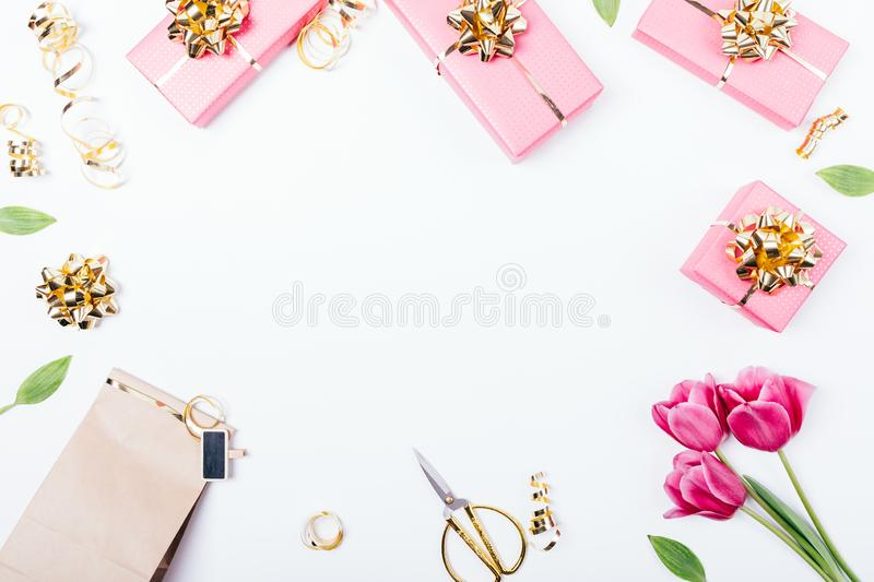 View from above on table with present boxes. Bows and ribbons to wrap. Flat lay frame composition of holiday gifts and bouquet of pink tulip flowers on white stock images
