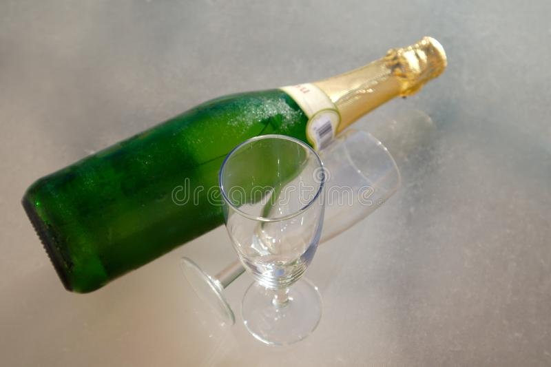 Two glasses next to a bottle of sparkling wine on a gray table royalty free stock photography