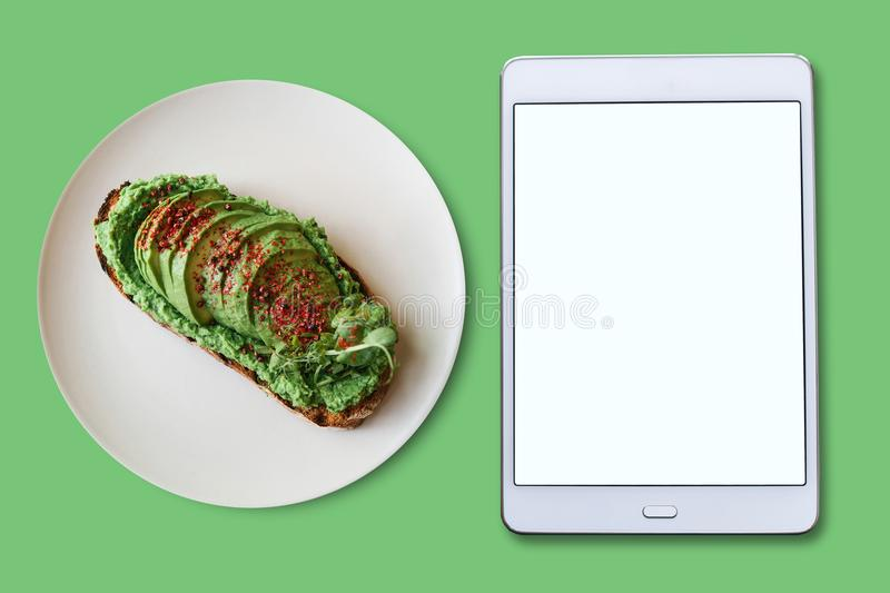 View from above. Tablet with blank screen for text. Next is a delicious and healthy vegetarian toast or an avocado royalty free stock images