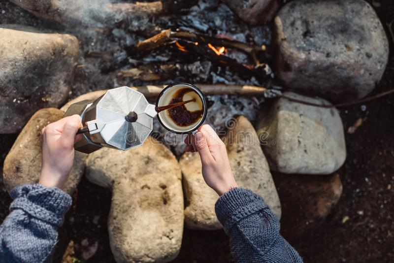 View from above of traveler woman pours itself hot beverage in mountains near to bonfire. Female sitting and holding a mug of coffee after hiking. Travel stock image
