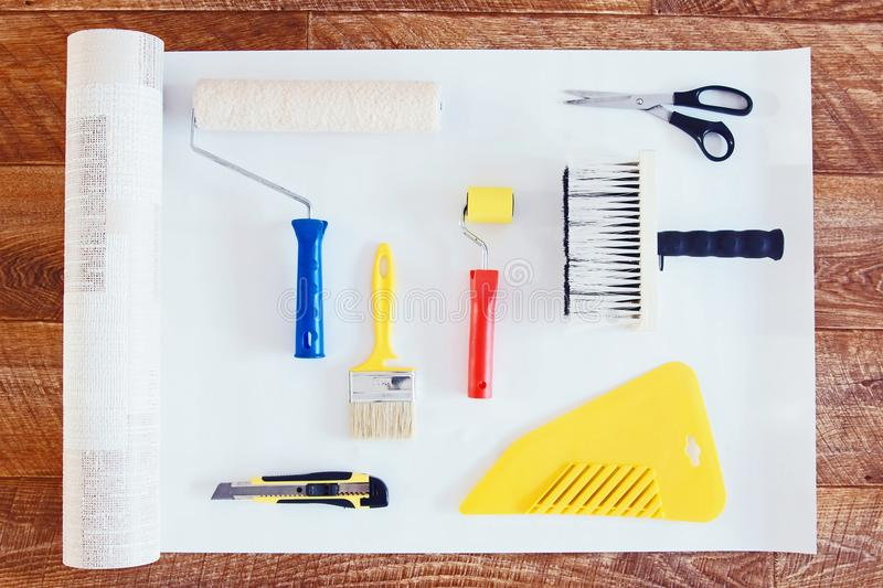 View from above at various tools for wallpapering and a roll of wallpaper. On wooden background stock photography