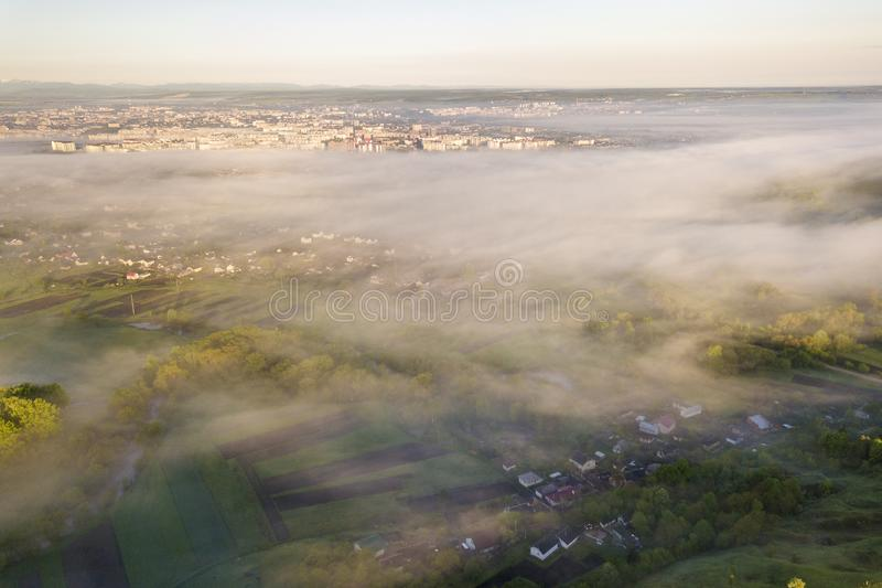 View from above of white fog on village house roofs among green trees under bright blue sky. Spring misty landscape panorama at stock image