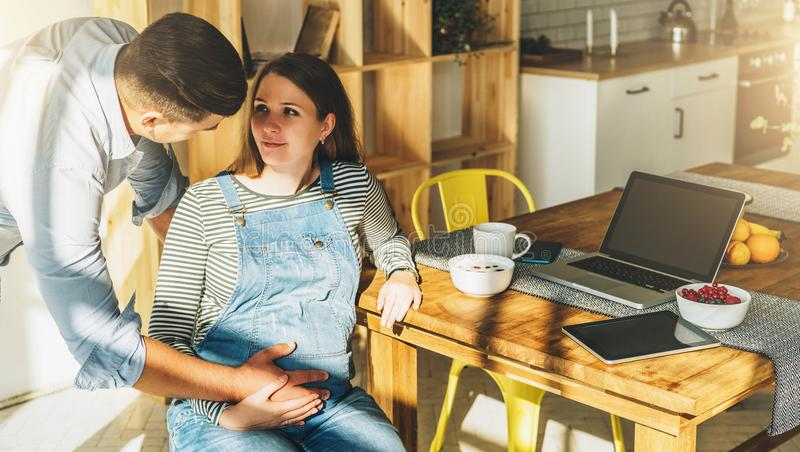 View from above.Young married couple in kitchen.Pregnant woman is sitting at table, man is holding her pregnant belly. stock photo