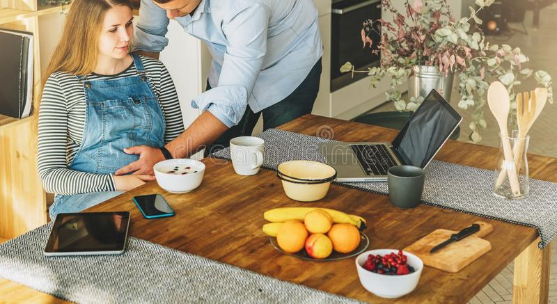 View from above. Young married couple in kitchen.Pregnant woman is sitting at table, man is holding her pregnant belly. royalty free stock image