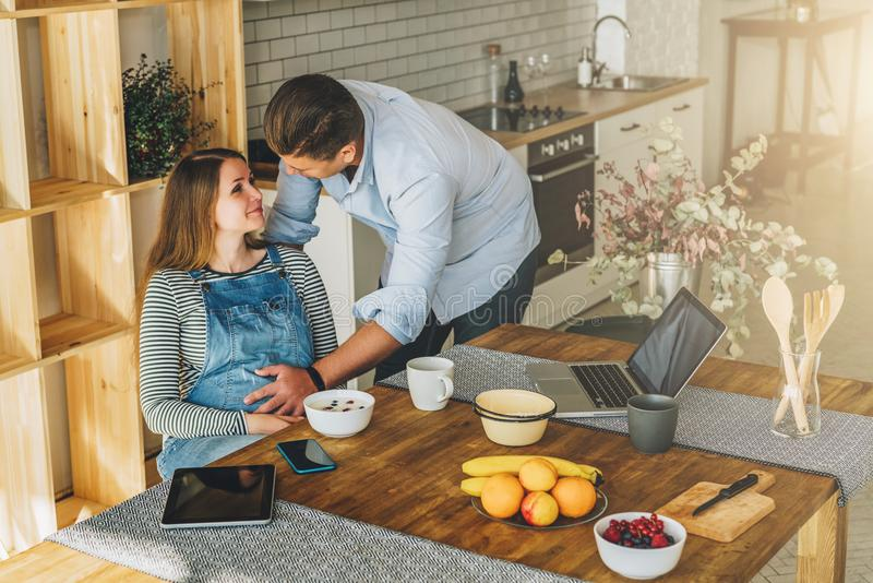 View from above.Young married couple in kitchen.Pregnant woman is sitting at table, man is holding her pregnant belly. royalty free stock photos