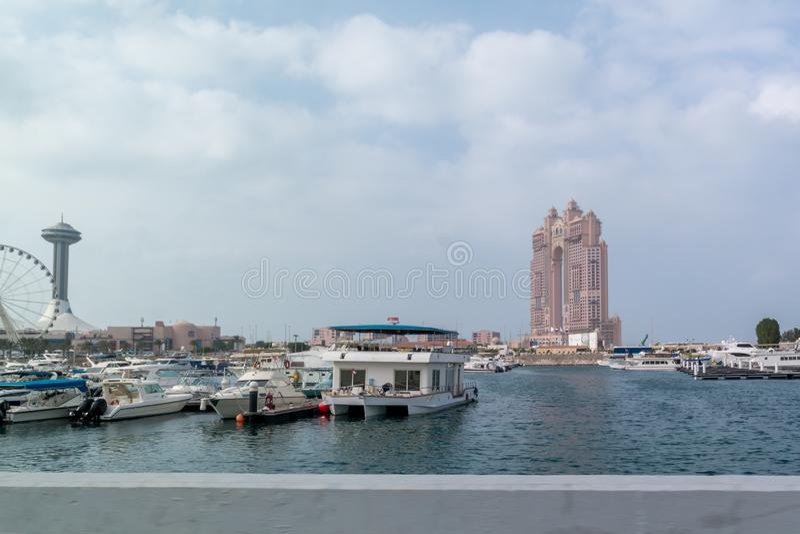 View of Abu Dhabi city famous Marina Mall, Marina eye wheel and Fairmont Marina Residences against cloudy sky.  stock photos