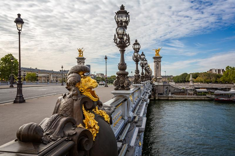 View across the Alexandre III Bridge with gilded statues and rows or ornate lamp in Paris royalty free stock image